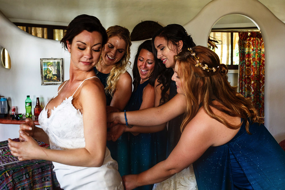 All bridesmaids helping the bride with the wedding dress