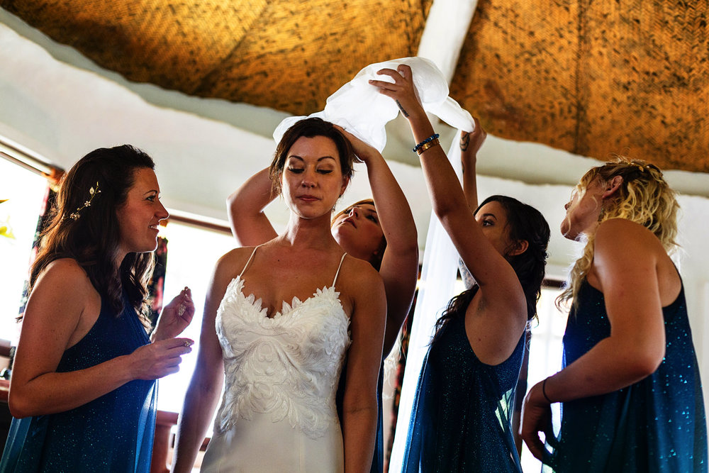 Bridesmaids helping the bride to put on the wedding veil