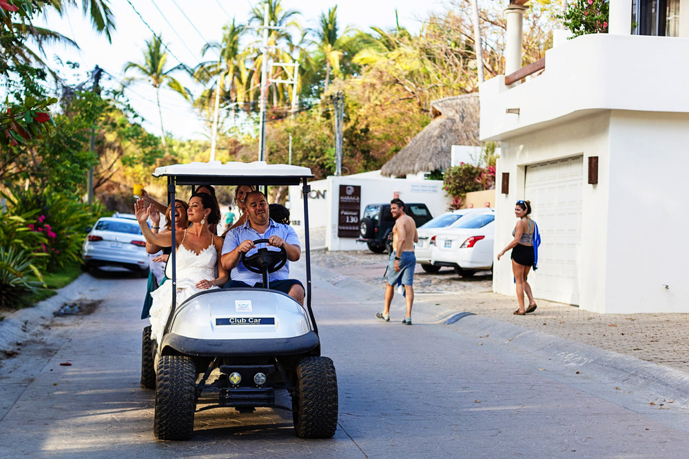 Bride and bridesmaids rolling on the streets of Sayulita in a golf cart towards the wedding ceremony