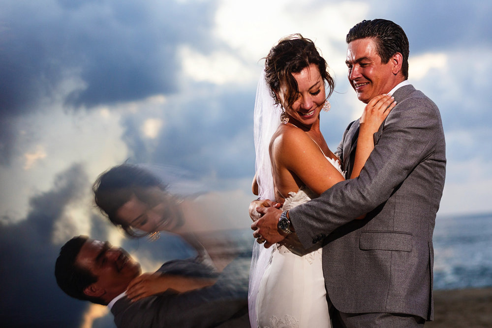 Bride and groom portrait on the beach with the sunset in the background and a prism reflection of the couple