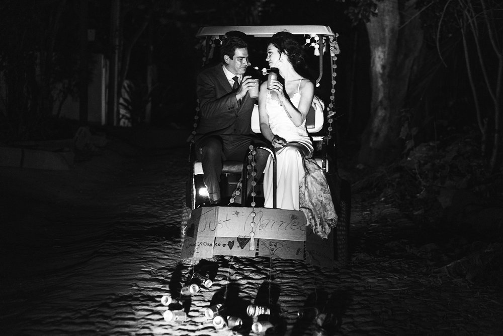 """Bride and groom exiting the wedding ceremony on a golf cart that has a """"just married"""" sign, while they cheer with beers"""