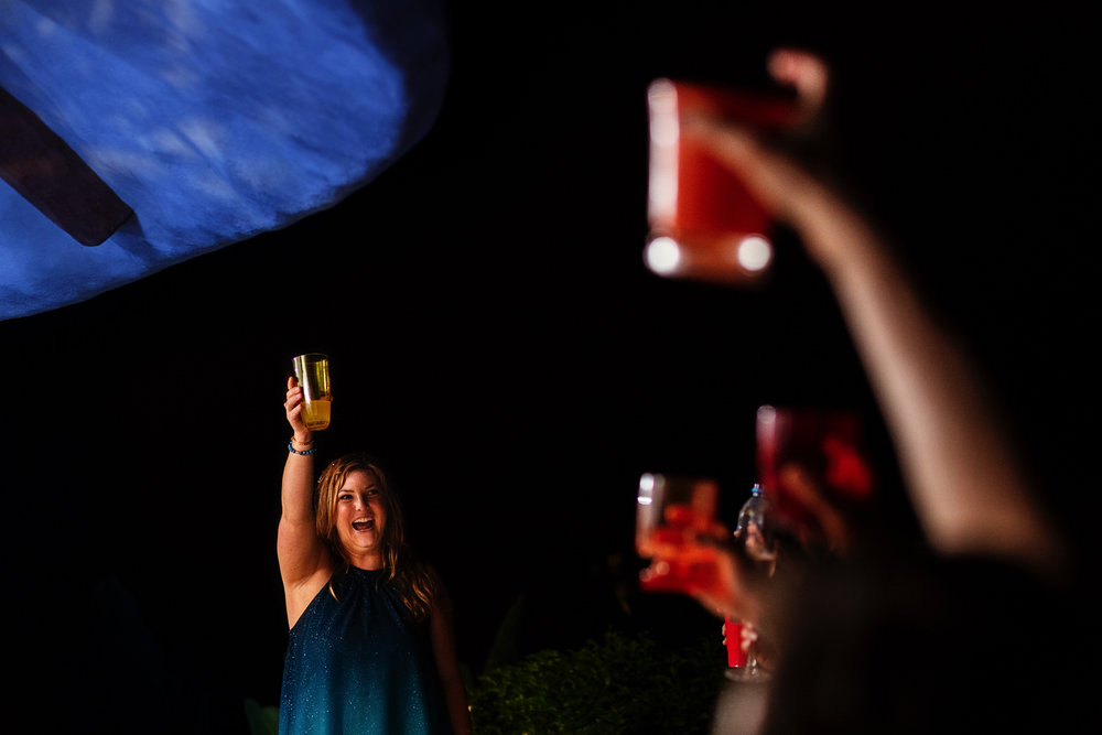 Bridesmaid toast and raised hands with red drinks