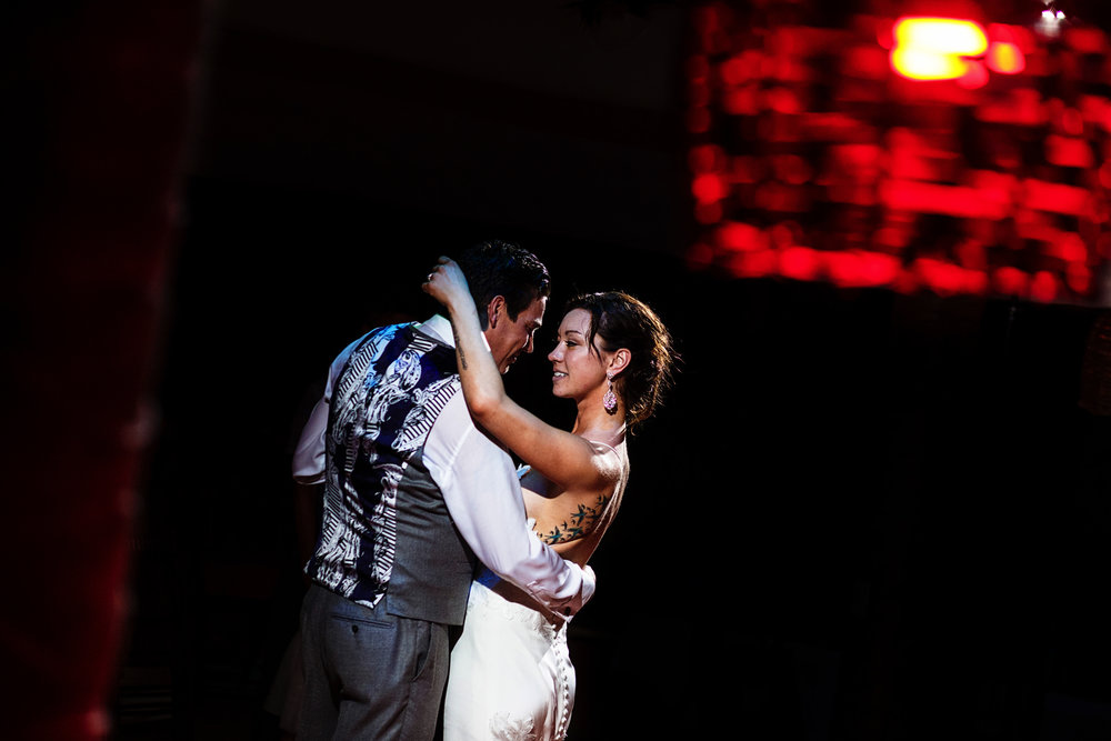 Bride and groom first dance through a column and a red lamp