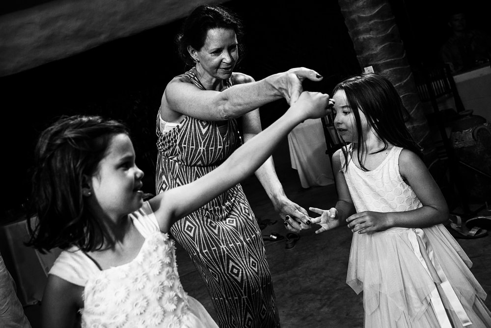 Adult wedding guest dances with two little girls in the dance floor at the party