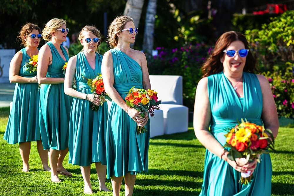 Bridesmaids walking to the aisle at the wedding ceremony wearing green blueish dresses and blue matching sunglasses