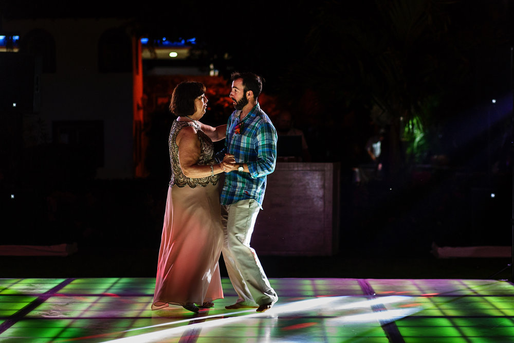 Groom dancing over an illuminated dance floor for the mother and son dance