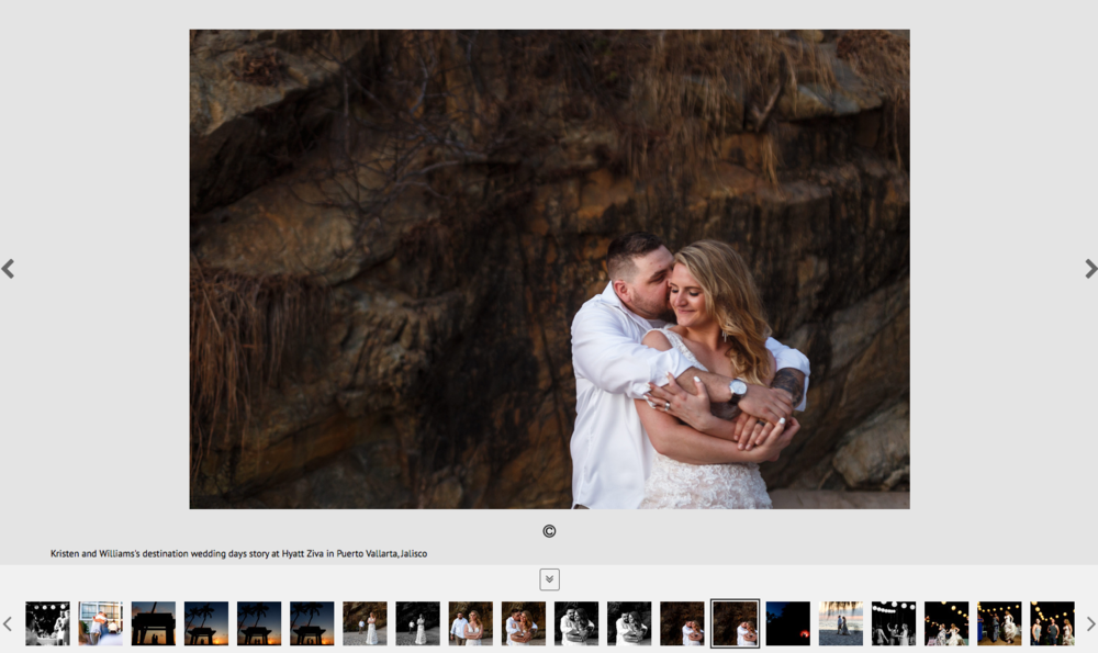 Groom hugs bride from behind with a big wall of rock behind them standing on the beach