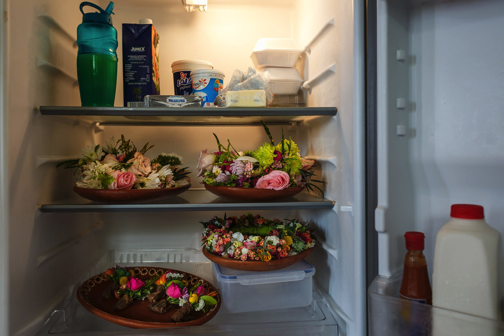 Bouquet, boutonnieres and other flowers stored in the fridge of the suite next to milk, juice and other groceries.
