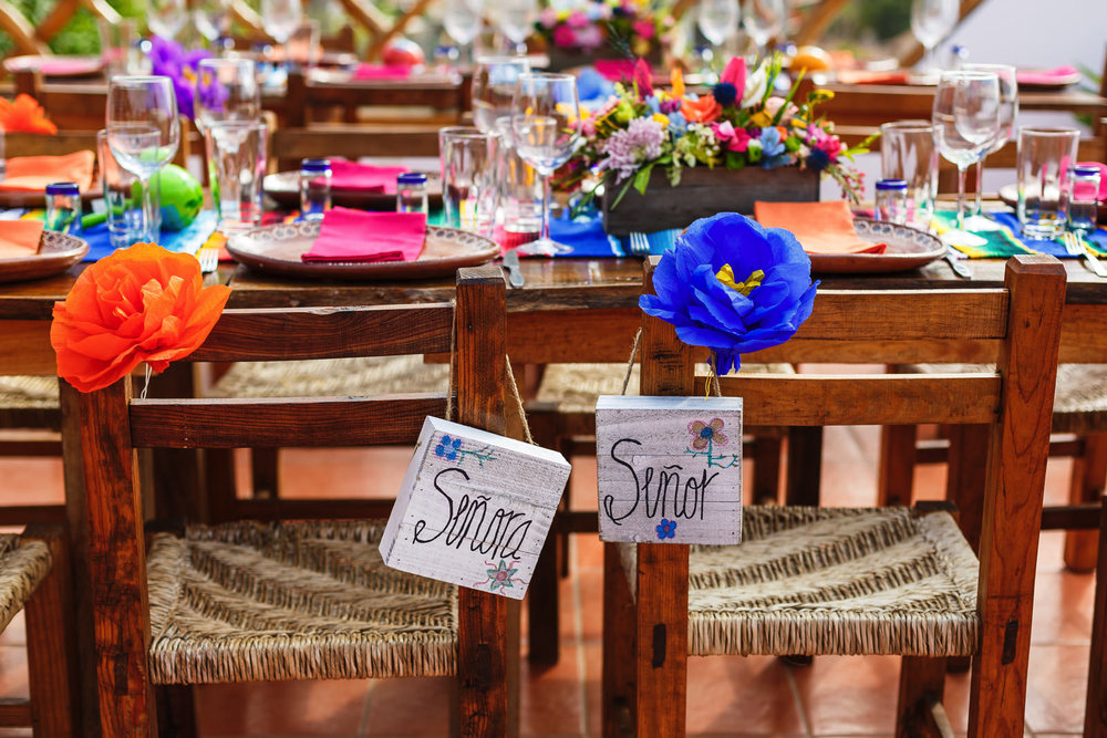 """Señor"" and ""Señora"" signs hanging on the groom and bride's chairs."