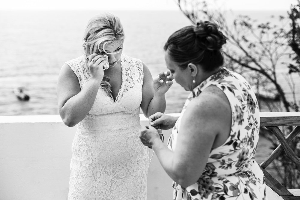 Bride crying after giving a bracelet to her mother.