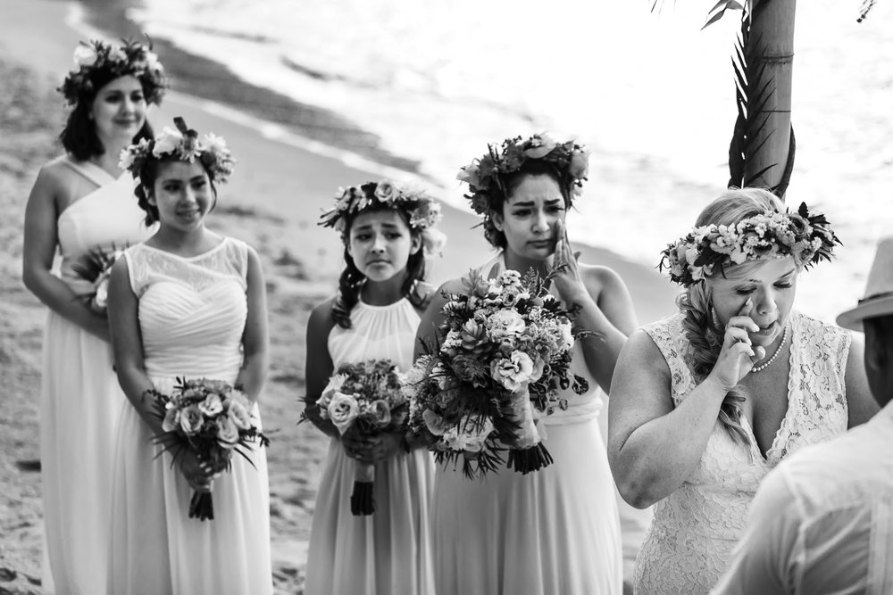 Bridesmaids crying and tearing up while bride reads her vows during the wedding ceremony.