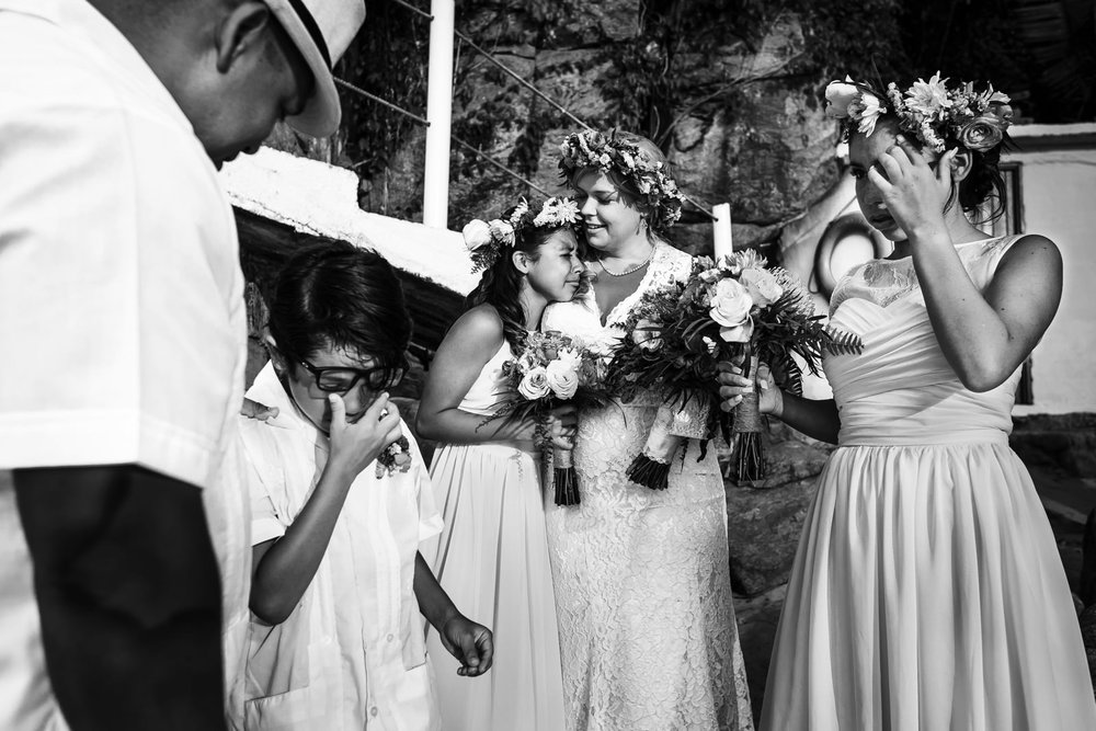 The whole family of the groom and bride crying together after the wedding ceremony.