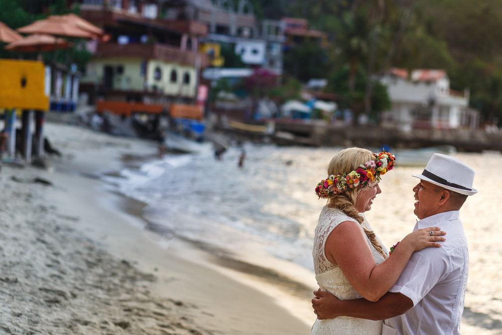 Bride and groom portrait on Yelapa's beach with a view in the background of the town houses.