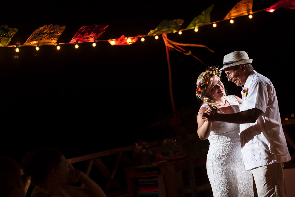 Bride and father dance on the Miramar terrace with papel picado flowing around them.
