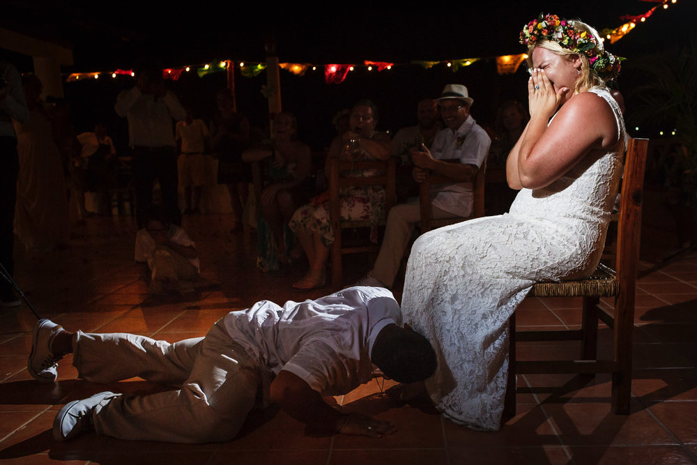 Groom drops into the ground for the garter removal at the bride's feet while she reacts shocked and embarrassed.