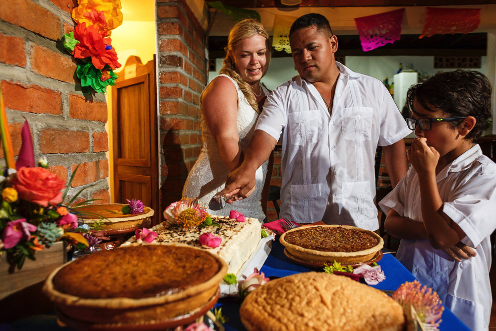 Bride and groom cutting the cake among all the famous and delicious pies from Yelapa, the little guy keeps and eye on all the sugar goodies.