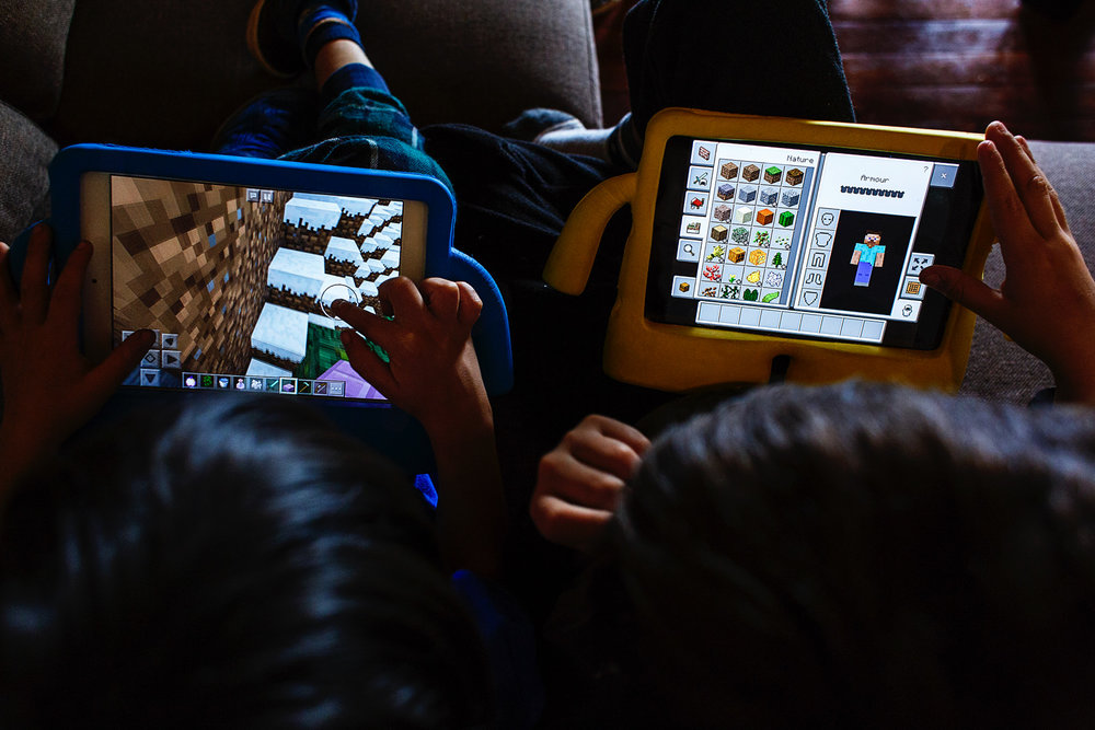 Two toddlers playing Minecraft on their iPads.