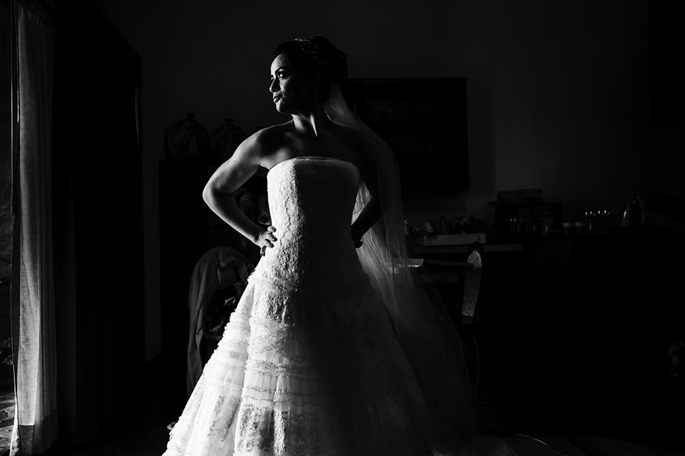 The bride poses for portraits near a window at her bedroom.