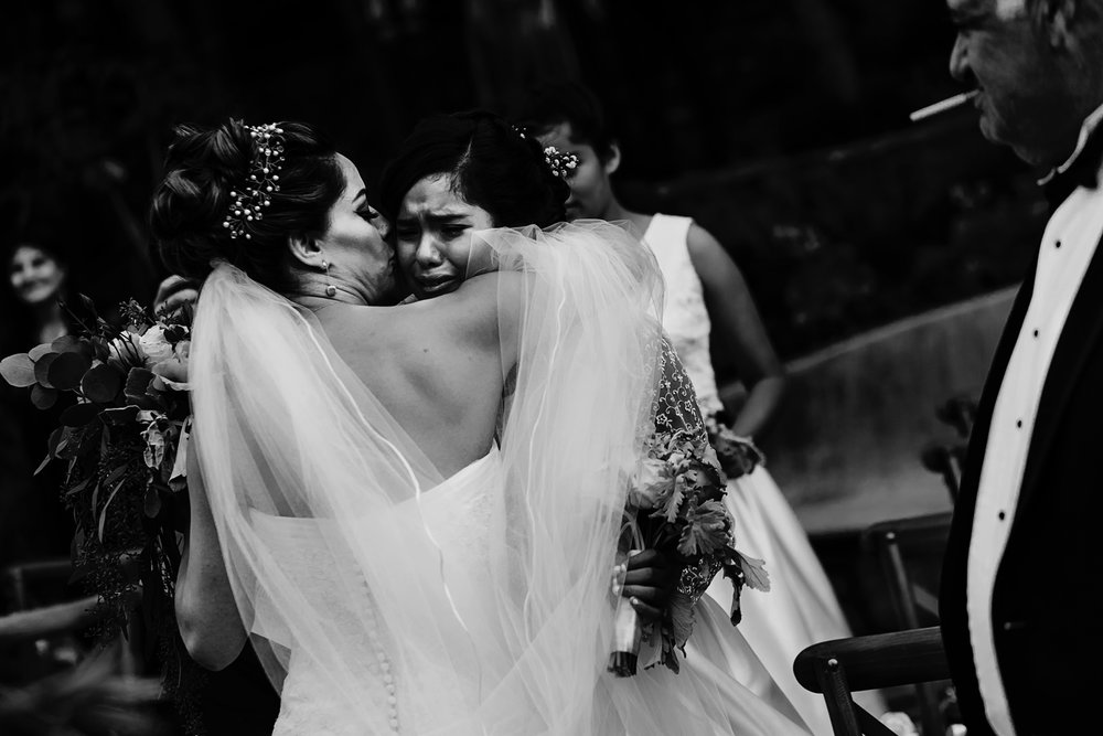 A niece of the bride cries in her arms at the end of the wedding ceremony.