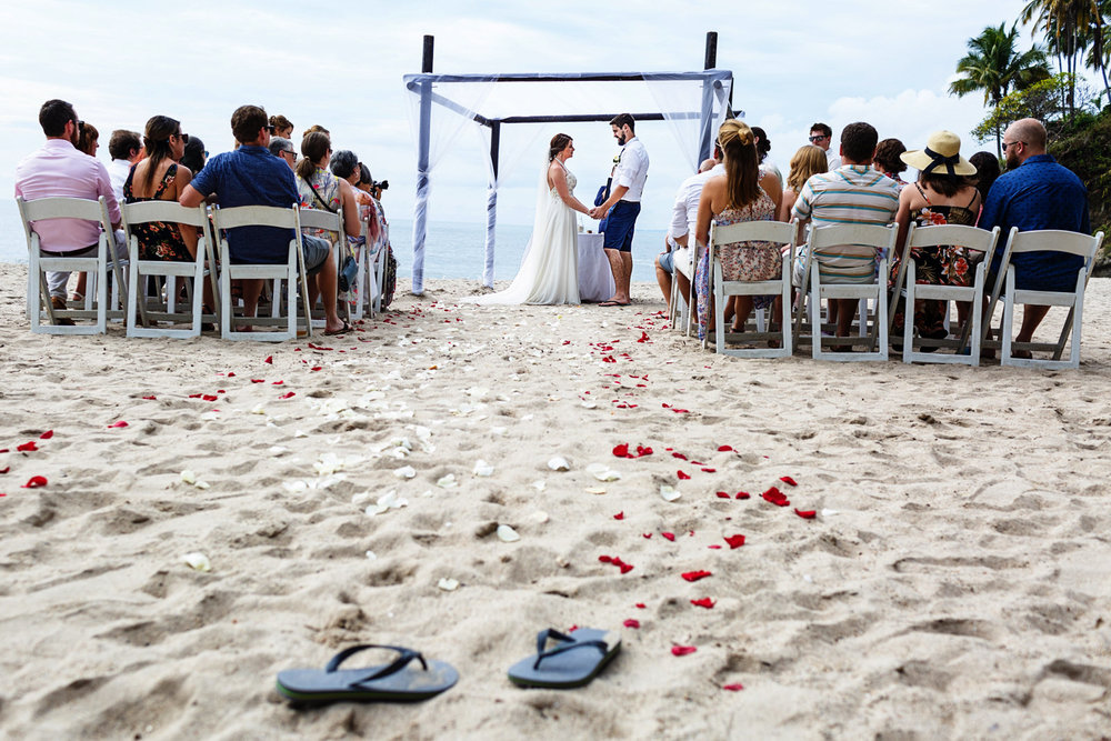 The bride left her flip-flops at the beginning of the aisle for the beach wedding ceremony.