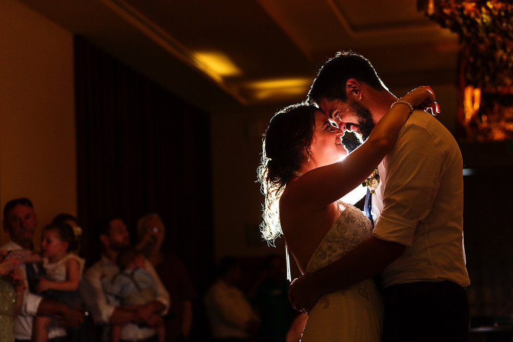 Bride and groom hug and put their nose and foreheads together during their first dance at the Hyatt Ziva ballrooms.