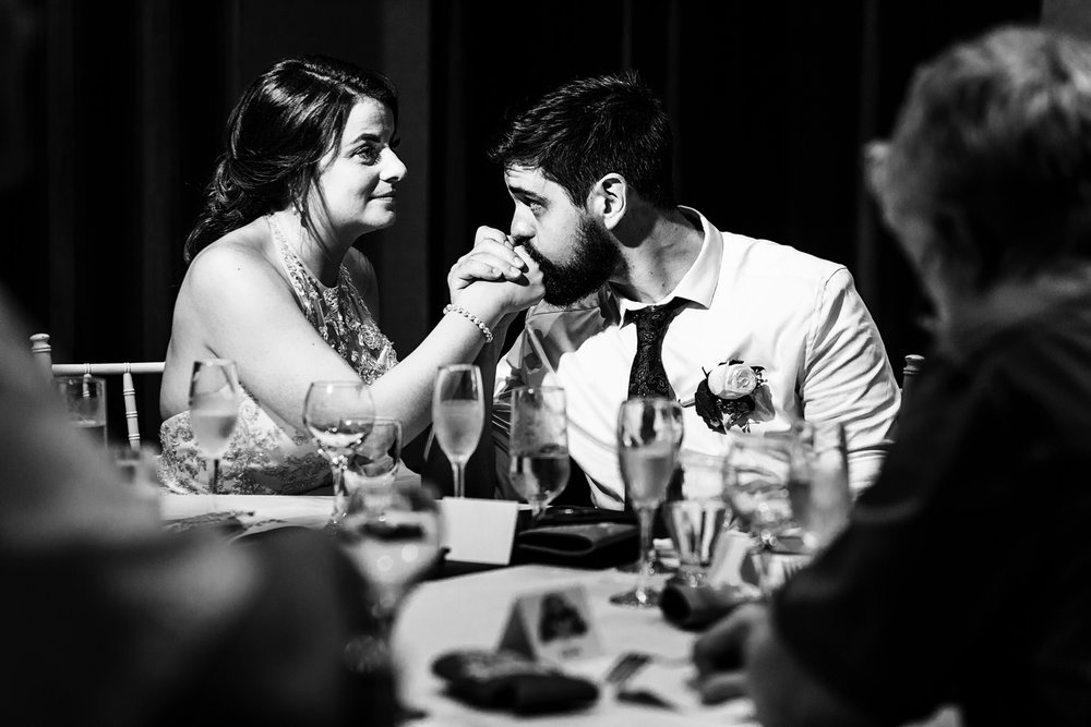 Groom kisses his bride's hand during the speeches at the dinner table.