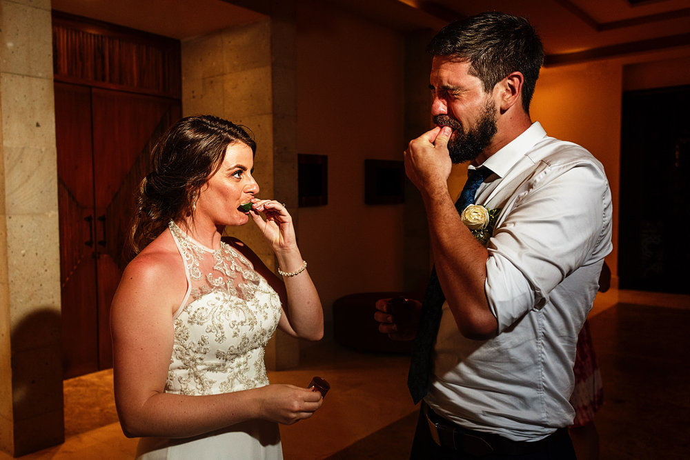 Groom and bride chewing on a slice of lime after having a tequila shot.