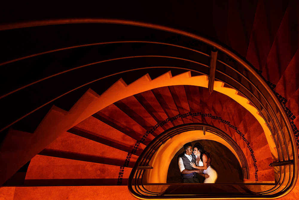 Bride and groom laying on the foot of a spiral staircase.