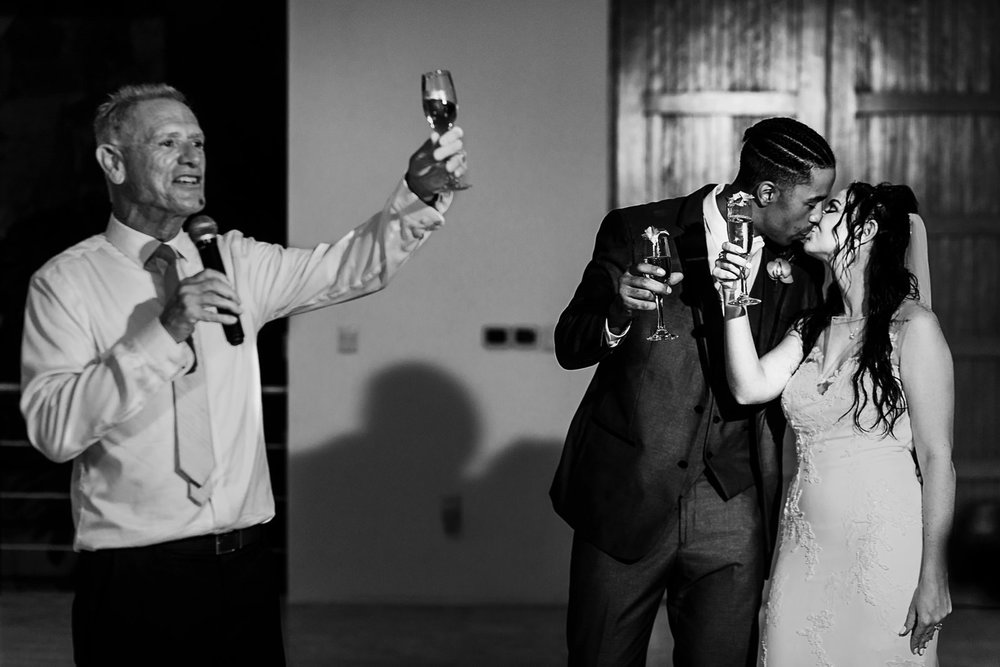 Dad raise his wine glass at the end of his toast, bride and groom kissing next to him.