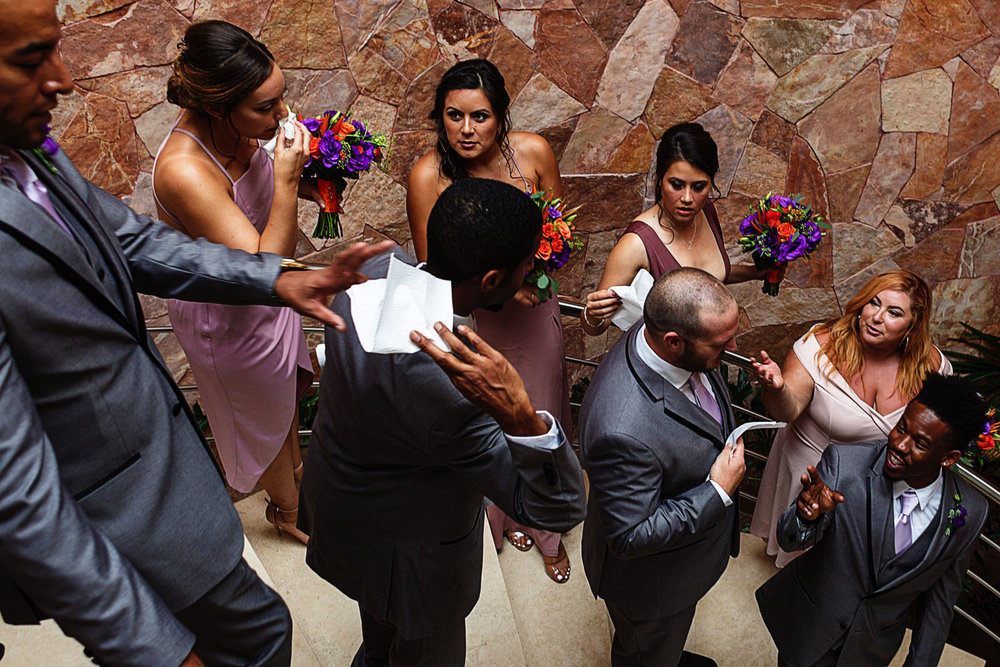 Bridesmaids and groomsmen passing around napkins to wipe their sweat on the staircase as they wait for the ceremony begins.