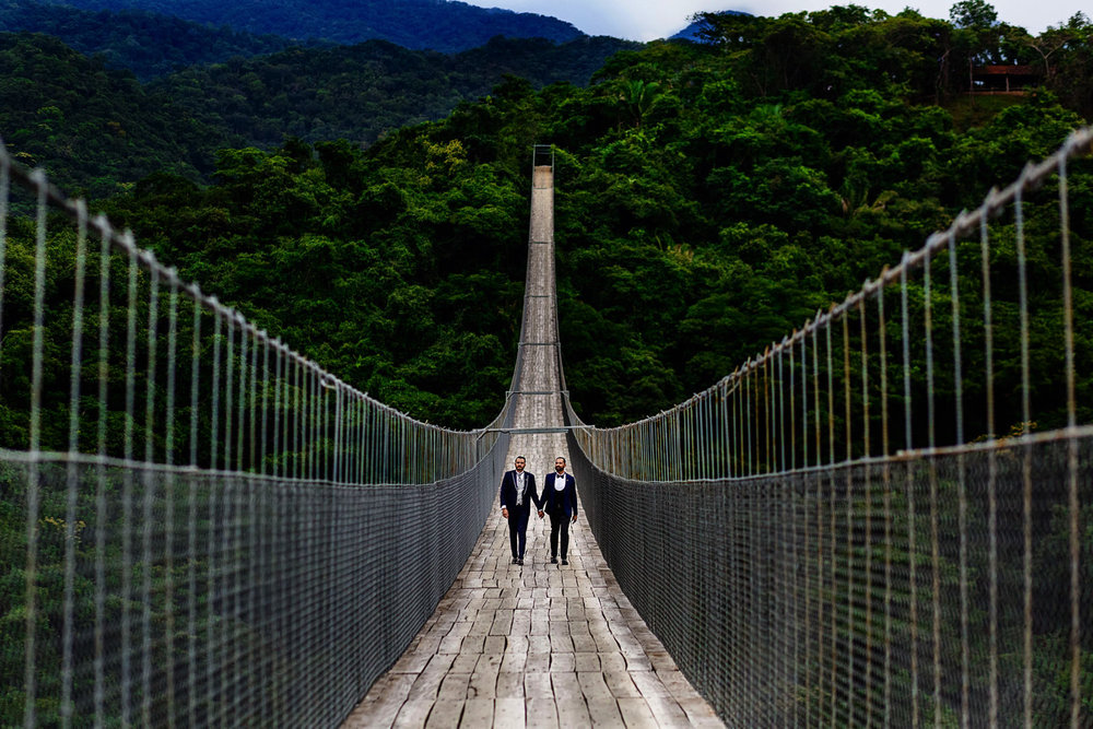 Gay couple wearing tuxedos walking over the Jorullo Bridge at the Canopy River park before their wedding ceremony.