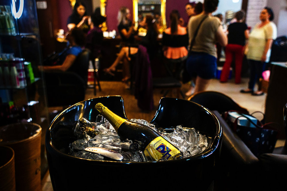 Bottle of champagne chilling on the head sink at a beauty salon during the ladies get ready before their gay couple friends's wedding