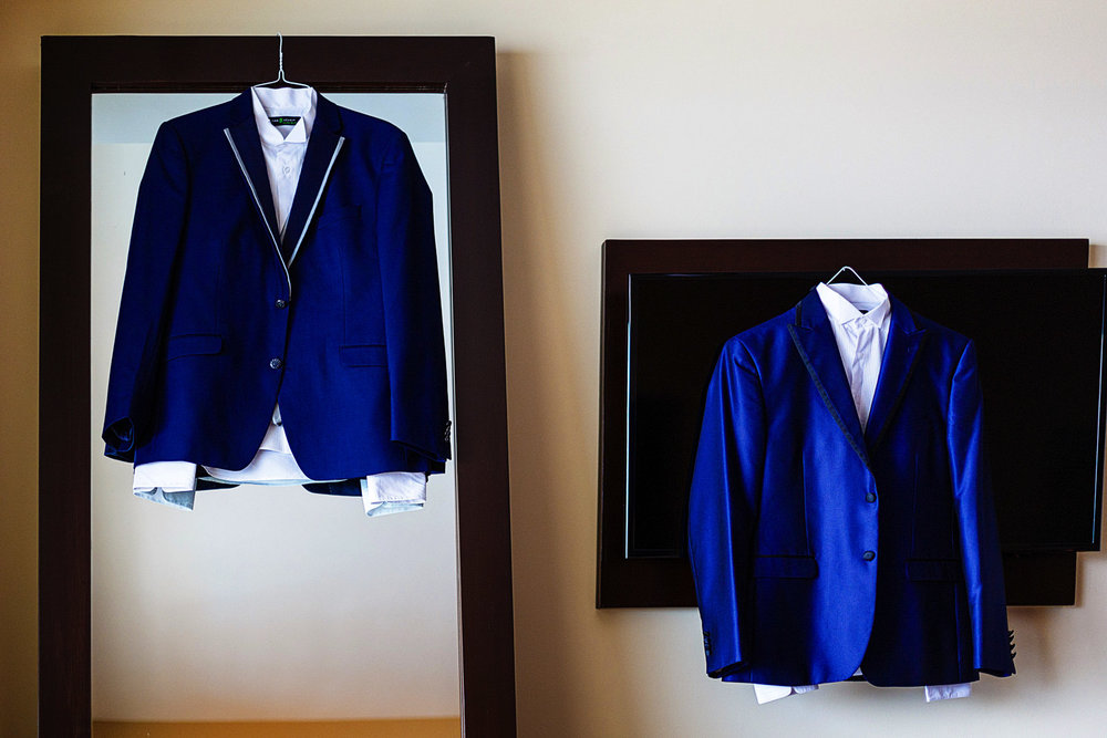 The grooms's tuxedos hanging on a TV and  mirror.
