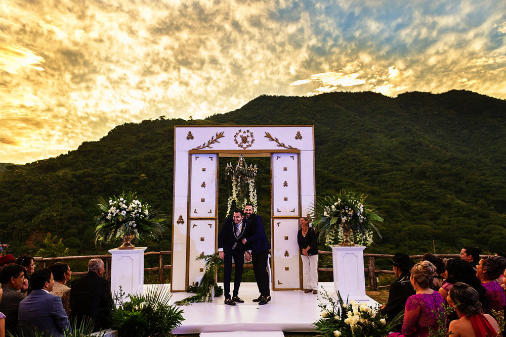 Gay couple at the end of their wedding ceremony during sunset.