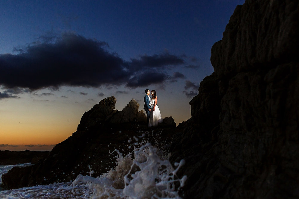 Couple over the rocks with waves crashing below them and the sun setting behind them.