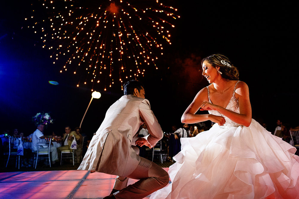 Bride and groom doing a surprise dance for all of their friends and family while fireworks light the sky.