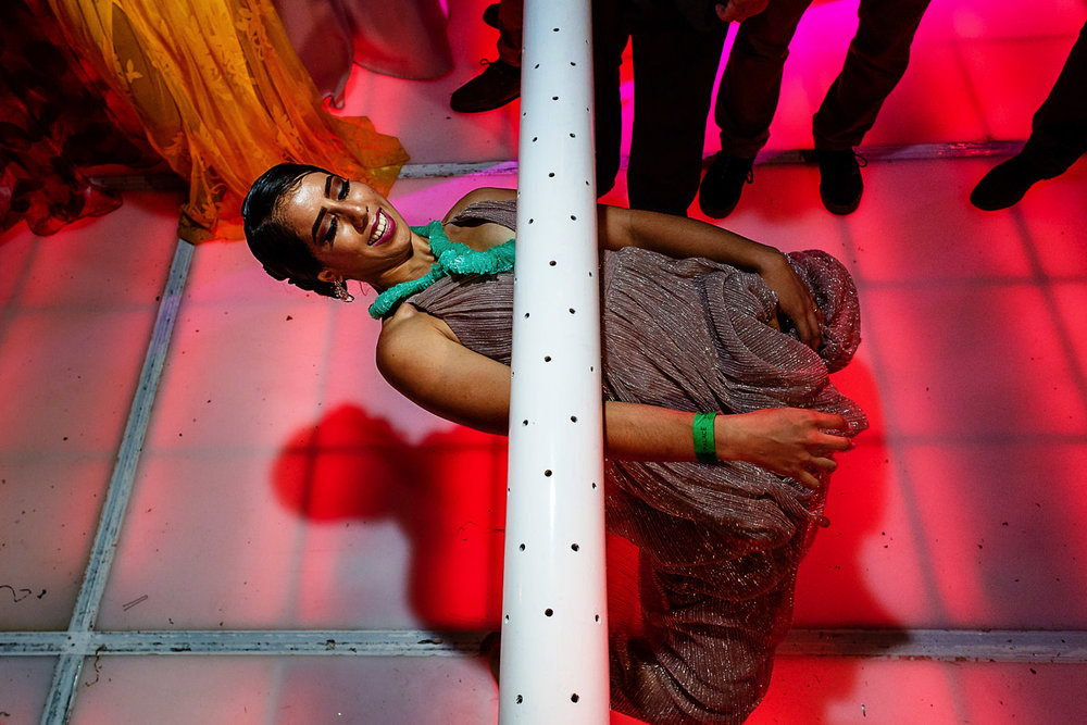 Girl going down below the limbo pole as low as possible.