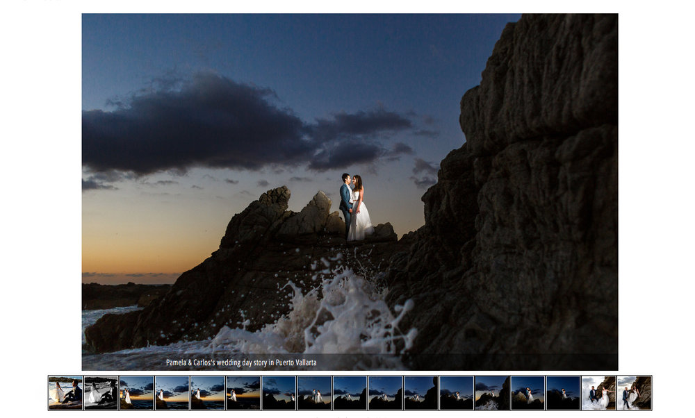 Groom and bride stand over the rocks near the ocean as a wave crashes and the sun sets behind them.