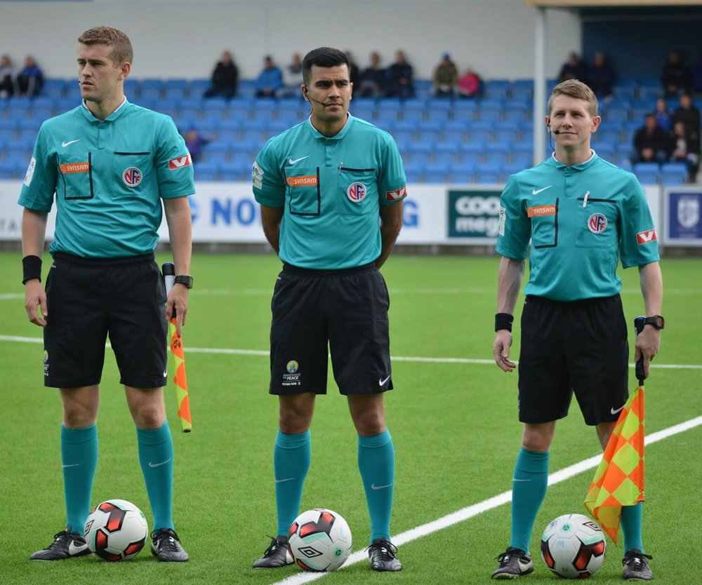 Isaak Bashevkin fra en kamp med hoveddommer Rohit Saggi og Jørgen Rønning Valdstadsve (t.v.). Også Saggi debuterer i Tippeligaen på søndag!