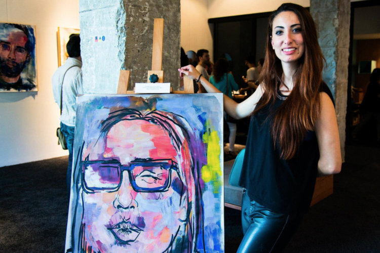 Clara Cabrera next to one of her paintings