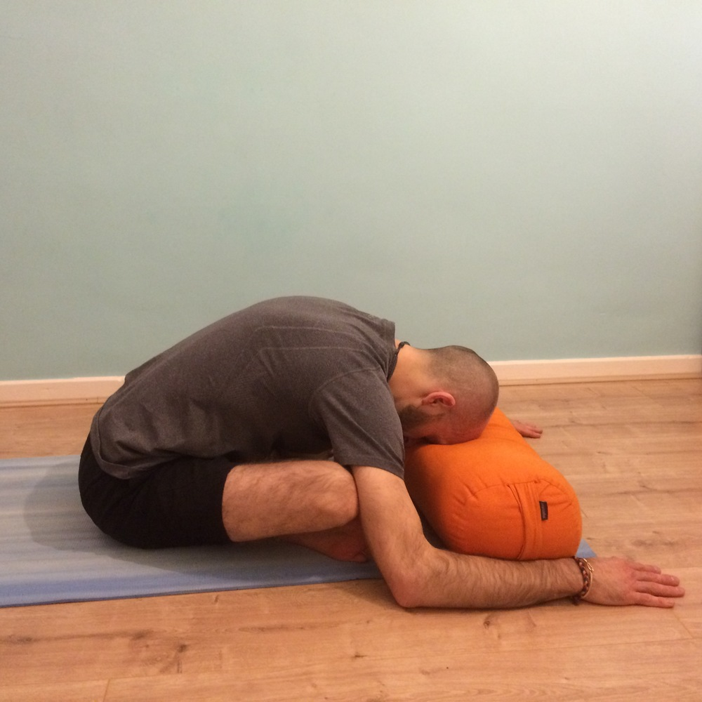 Sukhasana forward fold: 15 – 20 breaths each side Take a simple cross-legged posture and fold forward from the hips, resting your forehead on the floor or onto a pillow or bolster (as pictured here). If the hips are a little tight you can sit up on a prop to help find a greater sense of release.