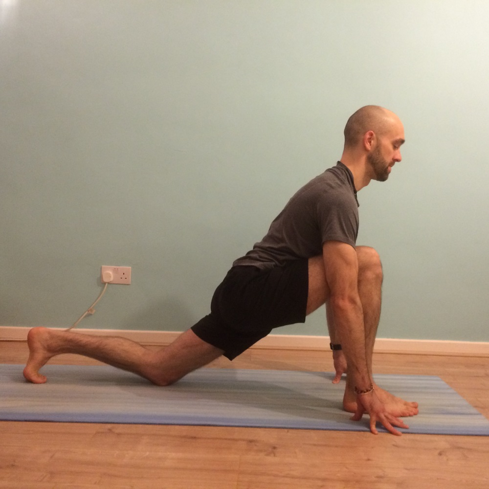 Low lunge (Anjaneyasana): 8 – 10 breaths each side Take a lunge position with the back knee released to the earth - resting on the bottom end of the femur rather than on the top of the kneecap (if the knee is sensitive double up the mat or use a blanket). Make sure that the front knee stays stacked over the front ankle, in line with your centre toes . Draw back on the fingertips and open your chest forward, breathing into the stretch through the front of your left groin. Take to both sides.