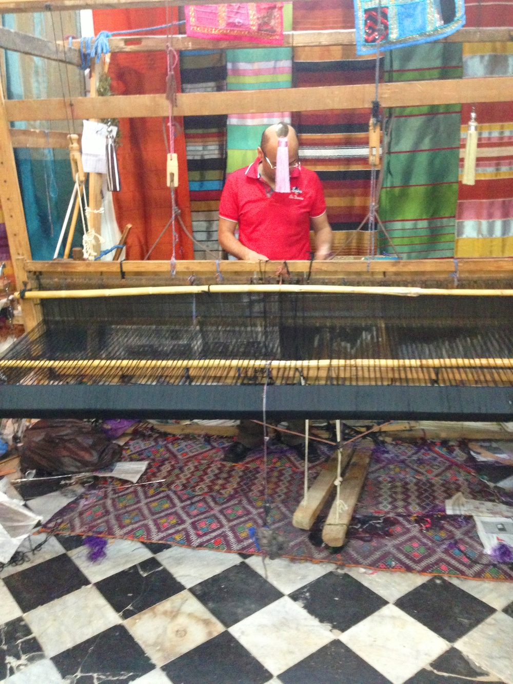 An artisan weaving threads at Berber Tissage