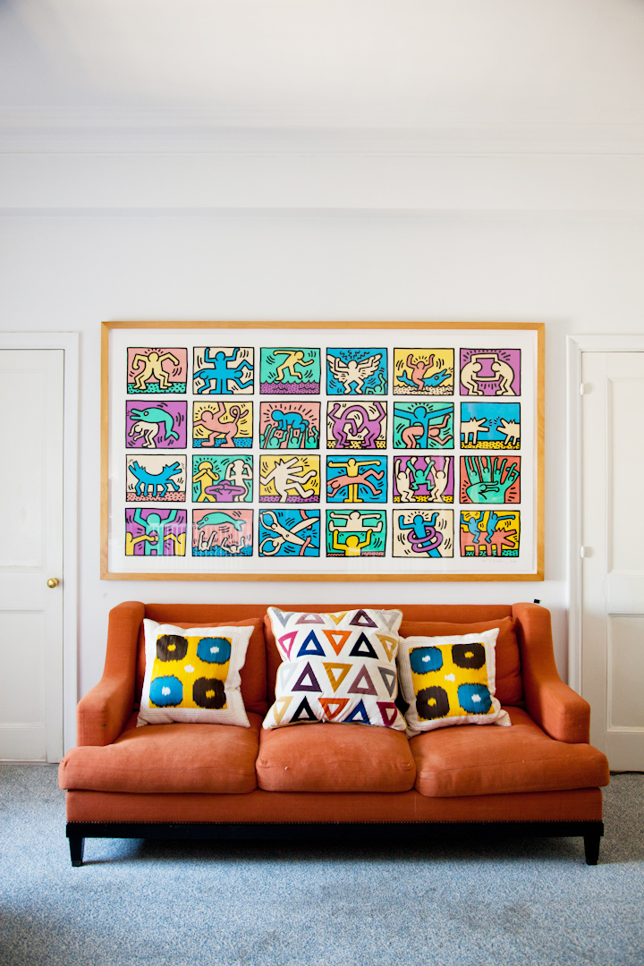 In Force and Olympia's bedroom, a gorgeous Keith Haring limited edition print on top of a muted-orange linen couch