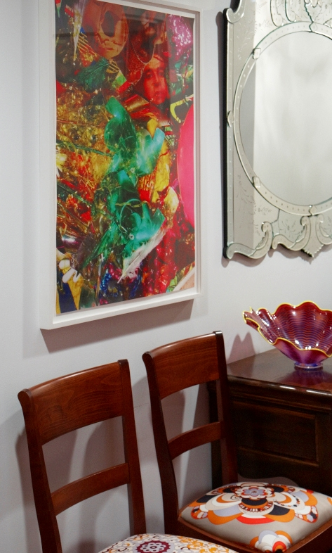 A pair of wood chairs whose seating cushions I got reupholstered with vintage Pucci scarves.  Assume Vivid Astro Focus limited edition photography on the wall.