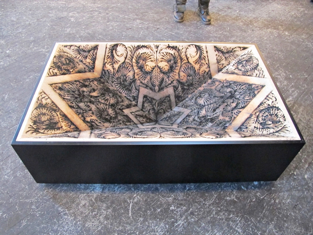 This table is the coolest thing.  It is drawn with gunpowder and then lit, thus creating the patterns that resemble tattoo ornaments and somehow, burned flesh too.