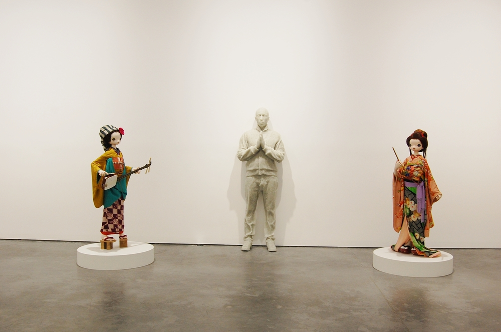 Daniel Arsham's broken glass and resin sculpture modeled with Pharrell's own body is flanked by two Chiho Aoshyma's sculptures
