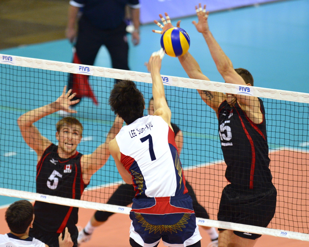 Captain Fred Winters with one of his six blocks of the match  Photo: Phil MacCallum FIVB/Volleyball Canada