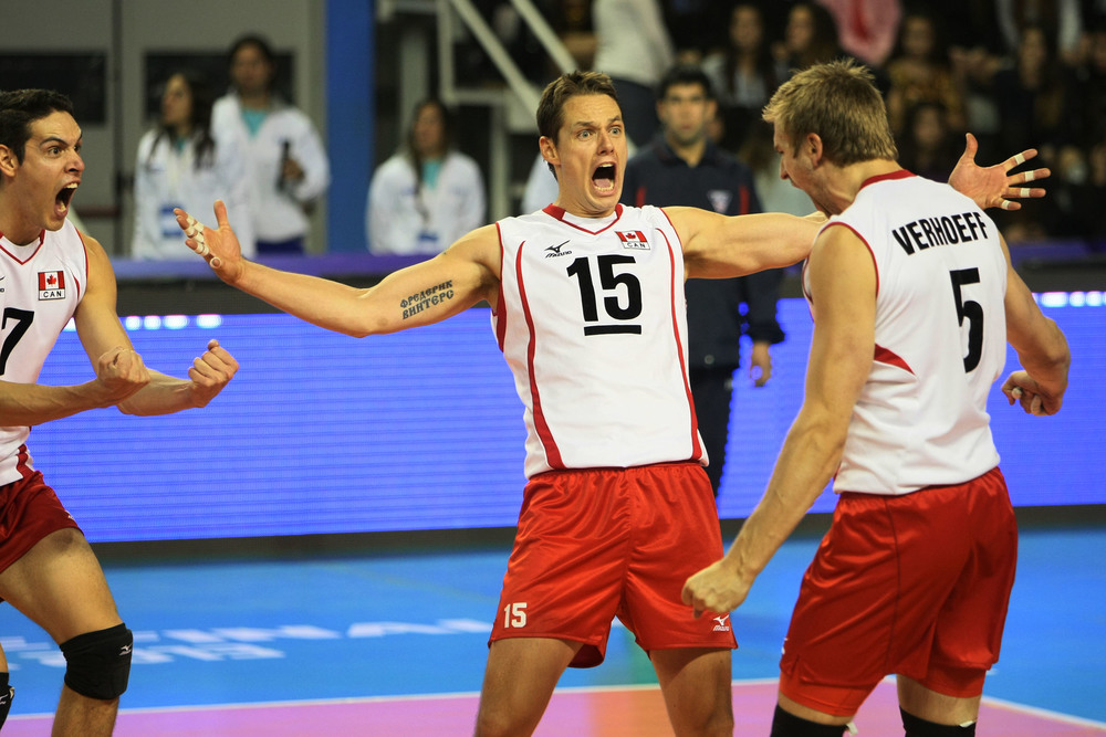 Canada's Dallas Soonias, Fred Winters, and Rudy Verhoeff celebrate a point against Russia.  Photo: FIVB