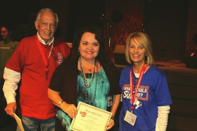 "Carolana receiving an award for the song ""Blessed by the Master's Hands"" from Sue C. and John Smith at the Write About Jesus Conference 2011."